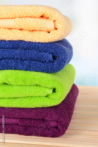 Bright towels on table on light background