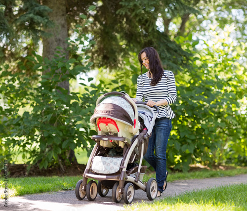 Woman Pushing Baby Carriage In Park