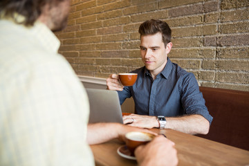Man and Friend in Coffee Shop Using Computer