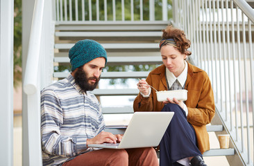 Hipster couple using computer and eating lunch outdoors