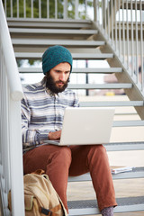 Young bearded hipster student using computer outdoors