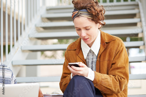Young redhead hipster woman using smartphone