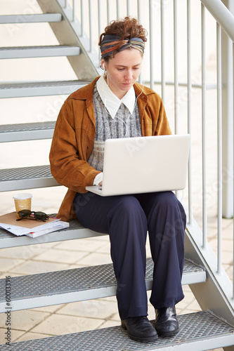 Young redhead hipster woman student using computer outdoors