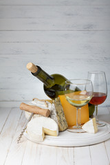 Cheese and wine on wooden table still life