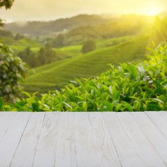 Empty wooden table with tea plantation on background