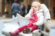 Cute toddler girl sits outdoor on wooden chair eating ice-cream