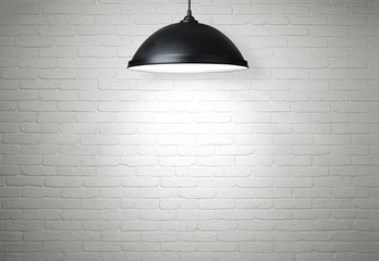 White brick wall illuminated by the lamp with copy space