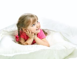 Portrait of a little girl lying in bed