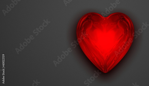 Red shiny reflective glass heart on grey background