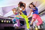 Fototapety young women in sport dress jumping at an aerobic and zumba exerc