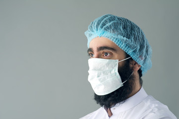 Male surgeon posing against a grey background