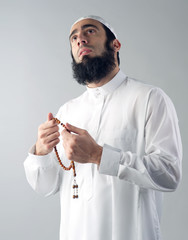 Arabian muslim man holding rosemary and praying