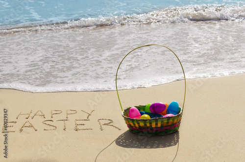 "Sign ""Happy Easter"" with basket on the beach"