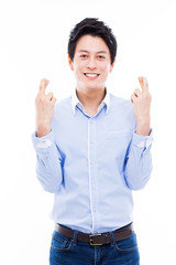 Young asian man showing lucky sign.