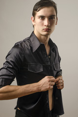 Sexy beautiful young man wearing a black shirt and undressing