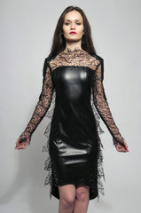 Beautiful brunette woman wearing a black dress and looking evil
