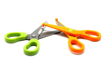 Green and orange scissors isolated on white background
