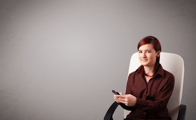 young lady sitting and holding a phone with copy space