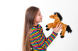 girl with long hair looking at a toy horse