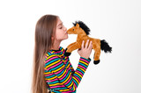girl kisses a toy horse