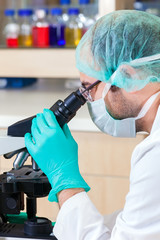 Male lab technician looking down a microscope.