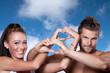 Young couple has joined hands in a heart shape