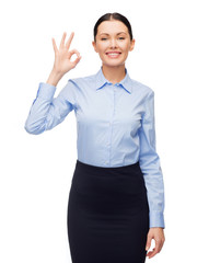 smiling businesswoman showing ok sign