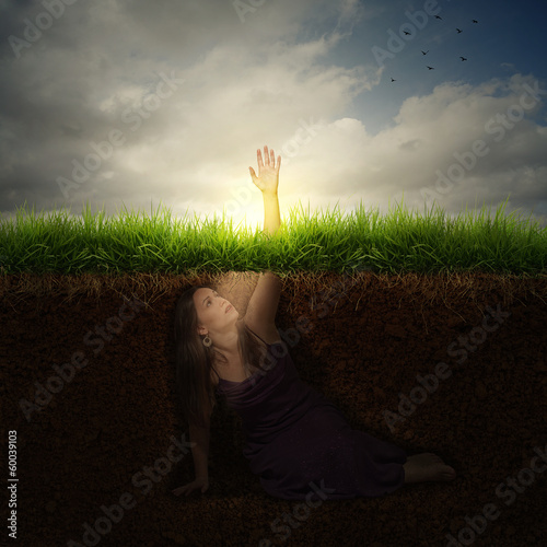 A woman buried under ground reaching out for help.