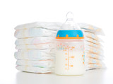 Child stack of diapers and baby feeding bottle with milk