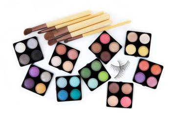 Various eyeshadow palettes, fake eyelashes and cosmetic brushes