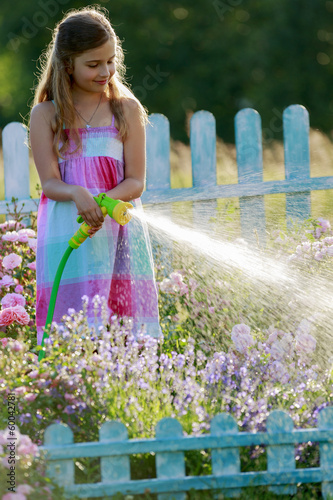Watering, flower garden - girl watering roses