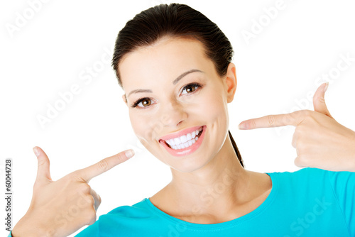 Beautiful woman pointing on her perfect white teeth.