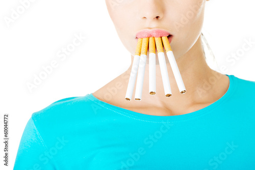 Young beautiful woman with cigarettes in mouth.