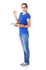Young casual student woman with book and pointing up.