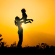 silhouette of a mother and son who play outdoors at sunset backg