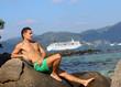 Парень на пляже на фоне корабля