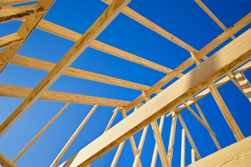 New construction home framing against blue sky