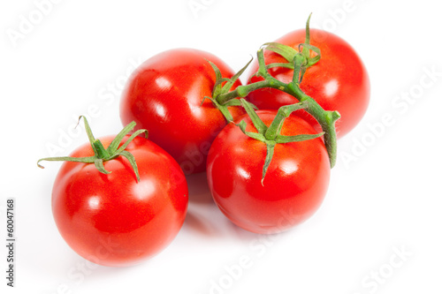 three fresh tomatoes with green leaves isolated on white backgro