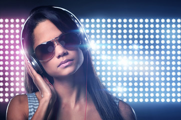 Sexy dj with headphones on light flares background