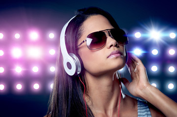 DJ woman with headphones and nightclub lights