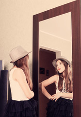 beautiful funny teen girl looking in the mirror