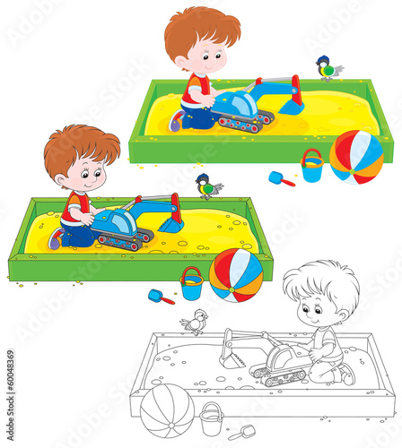 boy playing with a toy excavator in a sandbox