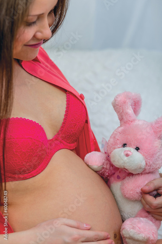 Pregnant woman in red underwear holding toy
