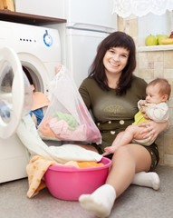 housewife with  baby putting clothes in to washing machine