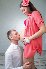 young man kisses the belly of pregnant wife in red