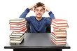 Angry stressed student sitting at his desk with hands on the hea