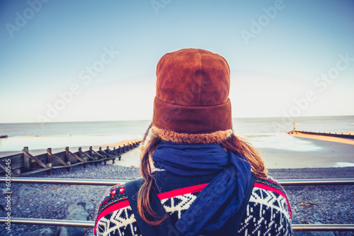 Rear view of woman in hat looking at sea