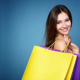 beautiful young woman with colored shopping bags over blue