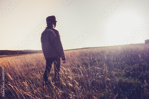 Young woman looking at sunset in field