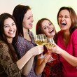 Happy young women friends touching the glasses with each other o
